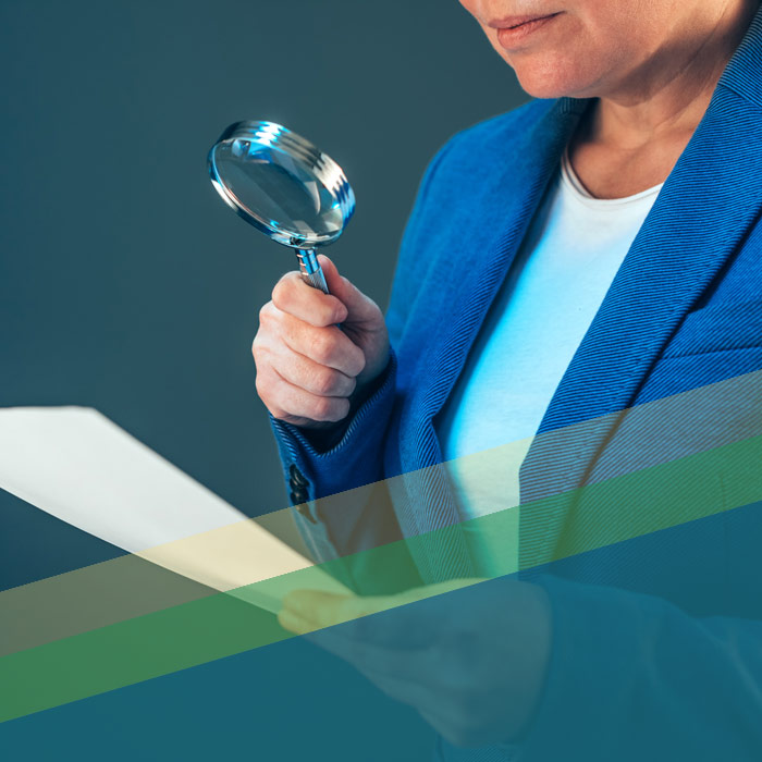 A White Woman's Hand Holding A Magnifying Glass Examining A Document