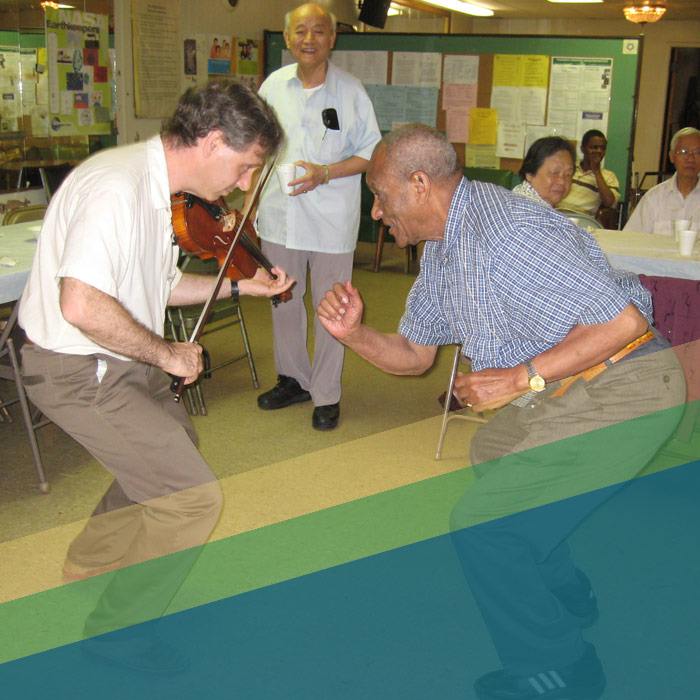 Man playing a fiddle and man dancing