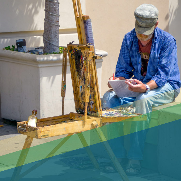 Man smoking a cigarette at a painting easel reading